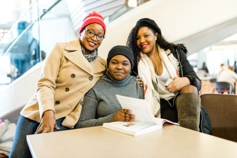 Three female international students studying inside wearing winter clothes.