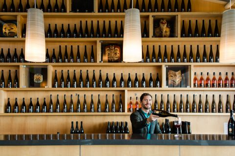 A male student is standing behind a wine sales bar and pours a glass of wine. Shelves of wine are behind him.