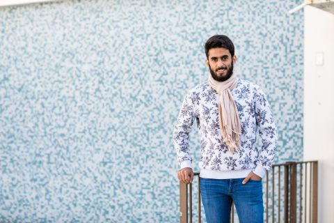 International male student wearing a wool scarf standing by a blue wall.