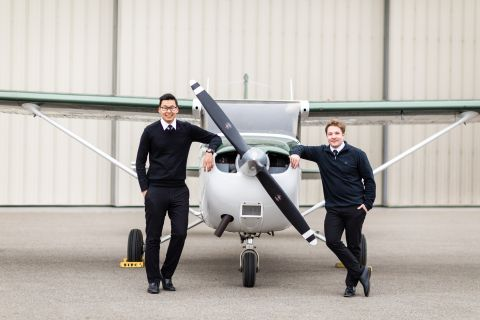 Two male commercial aviation students leaning on either side of a small propeller plane.
