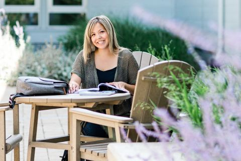 Indigenous female business student studying outdoors at a wooden table.