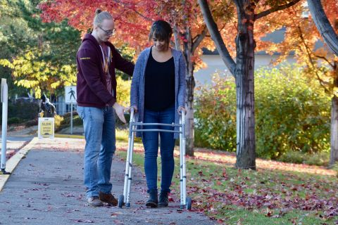Student practises supporting a patient using a mobility aid