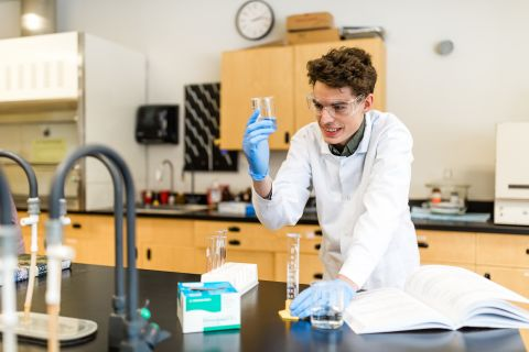 Chemistry student works with beakers in the lab