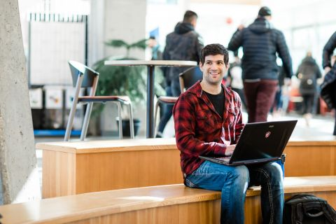 Computer Information Systems student studies on his break in a campus lounge area