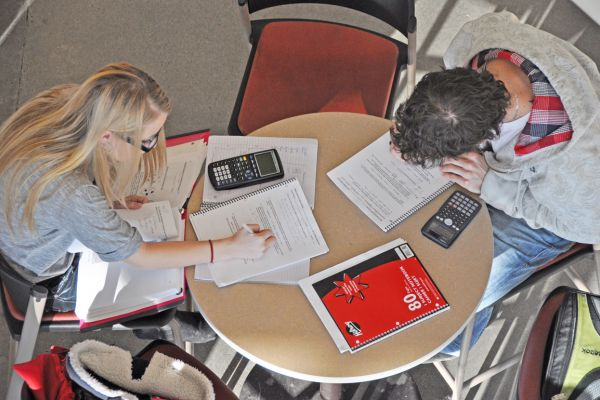 One male and one female student sitting at a round table with notebooks and calculators