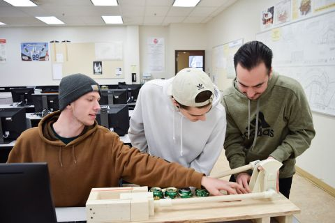 three students working on mechanical engineering project