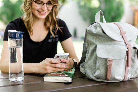 Student sitting at table with a phone and backpack