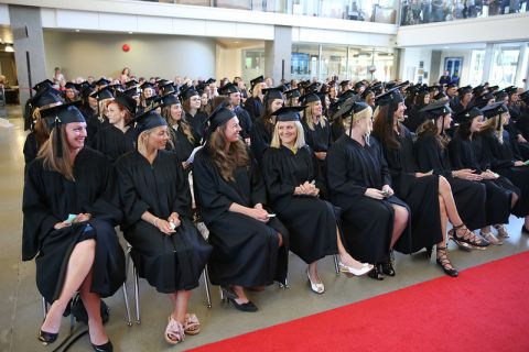 Students sitting at ceremony in caps and gowns