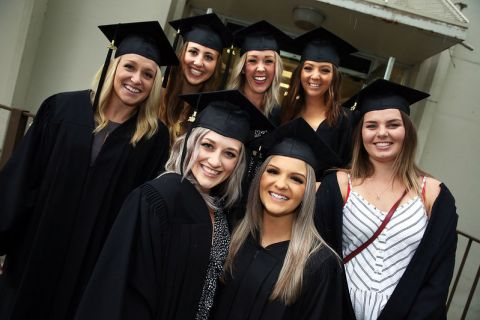 group of female students after graduation in caps and gowns
