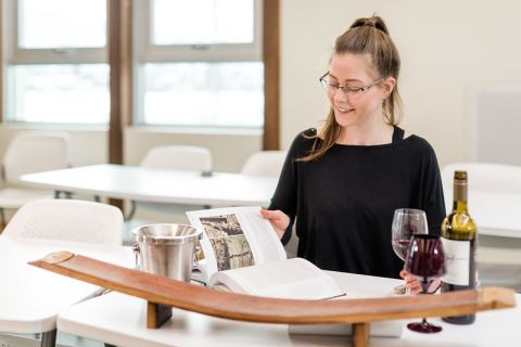 Female student tasting wine and reading a viticulture studies book