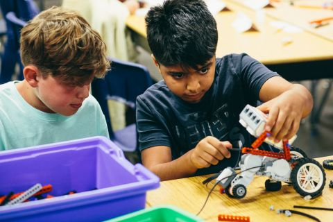 two male camp oc students building a small robotic vehicle