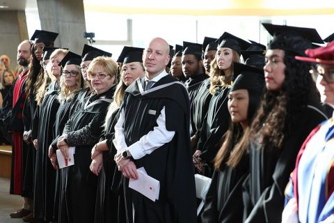 faculty standing for ceremony in gowns and caps