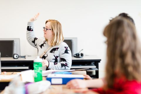 Adult Special Education student raises her hand in class.