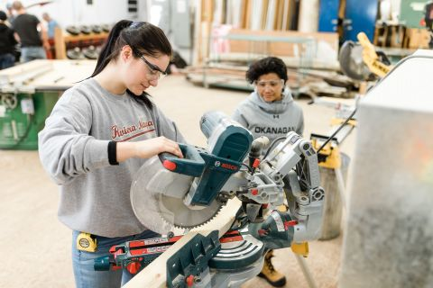 Two female Carpentry students cutting wood on chopsaw