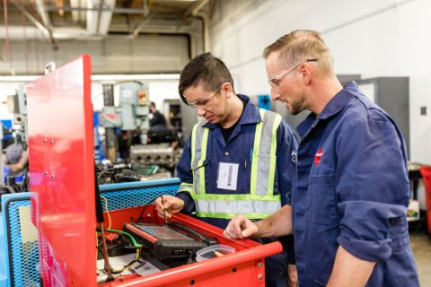 Automotive student uses diagnostic instruments with the help of an instructor