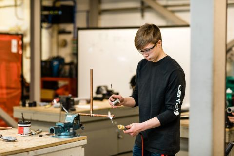 Apprentice heats up a piece of copper pipe with a torch