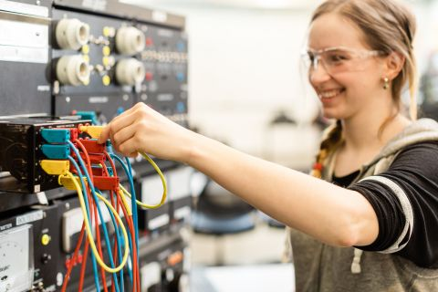 An industrial electrician apprentice works on connections in the lab.