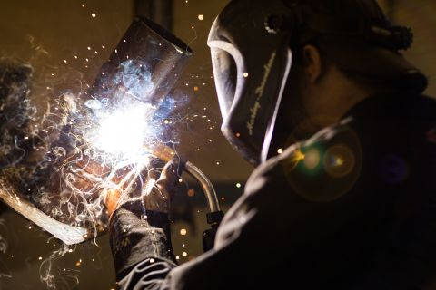 Welding student watches closely as two metals are welded together amidst sparks