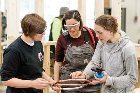 Three Women in Trades Training students review their pipefitting work together