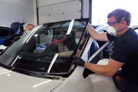 Automotive glass apprentices remove a windshield on a vehicle.