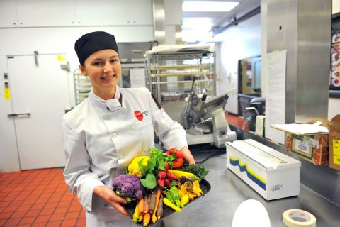 Culinary Arts student holding a platter with a colourful array of vegetables.