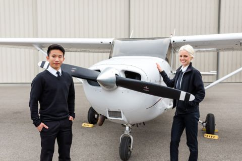 A male international student and a female student stand in front of a small airplane.