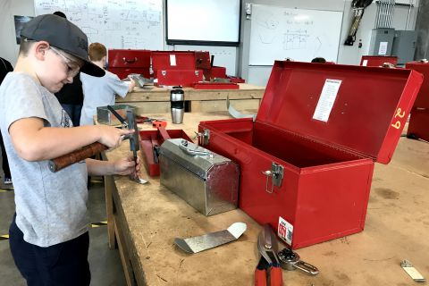 young boy using sheet metal hammer on tin tool box project while working on a bench