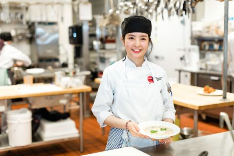 A female Culinary Arts student smiles as she holds a garnished bowl of soup.