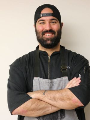 Alumnus Adam Relvas stands in front of a wall wearing a backwards hat and chef's coat.