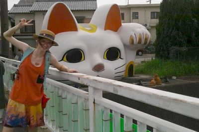 Arts student Xenon Tyner poses with a large cat shrine in Japan.