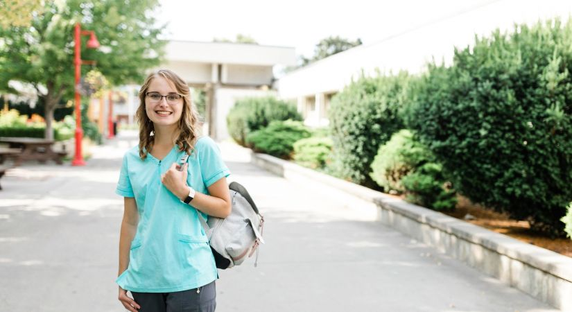 Student Mariah Perry stands in the Kelowna campus courtyard clutching her backpack in nursing scrubs