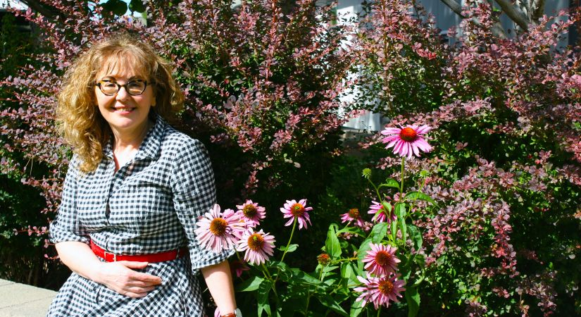 Political Science Professor Ayla Kilic relaxes in the garden with flowers behind her